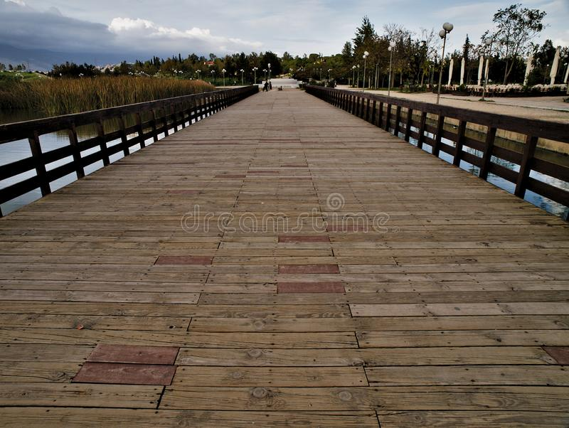 Pedestrian wooden bridge in a park. Pedestrian wooden blocks bridge in a park , perspective photo. Bridge above lake in a park. Tritsis enviromental park in royalty free stock photo