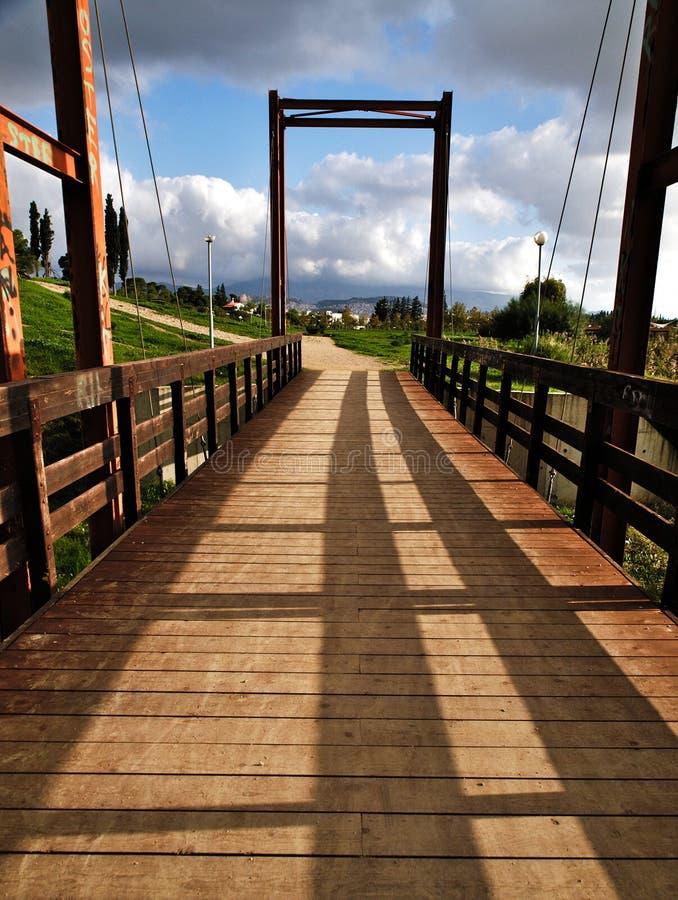 Pedestrian bridge in a park. Pedestrian wooden blocks bridge in a park , perspective photo. Bridge above lake in a park. Tritsis enviromental park in Athens royalty free stock photos