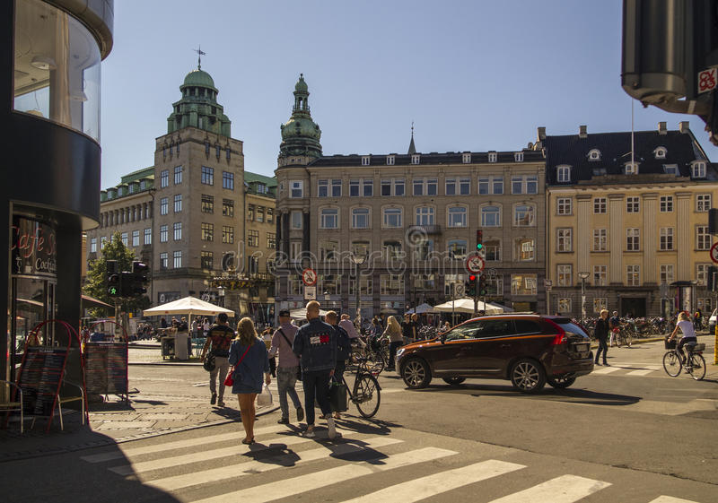 Pedestrians in central Copenhagen Old Square .Denmark. Pedestrians in central Copenhagen Gammeltorv Old Square and Caritas Fountain in Copenhagen, Denmark.The royalty free stock photography