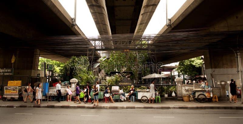 Pedestrians chodzą ulicznymi karmowymi kramami pod mostem w Bangkok zdjęcia stock