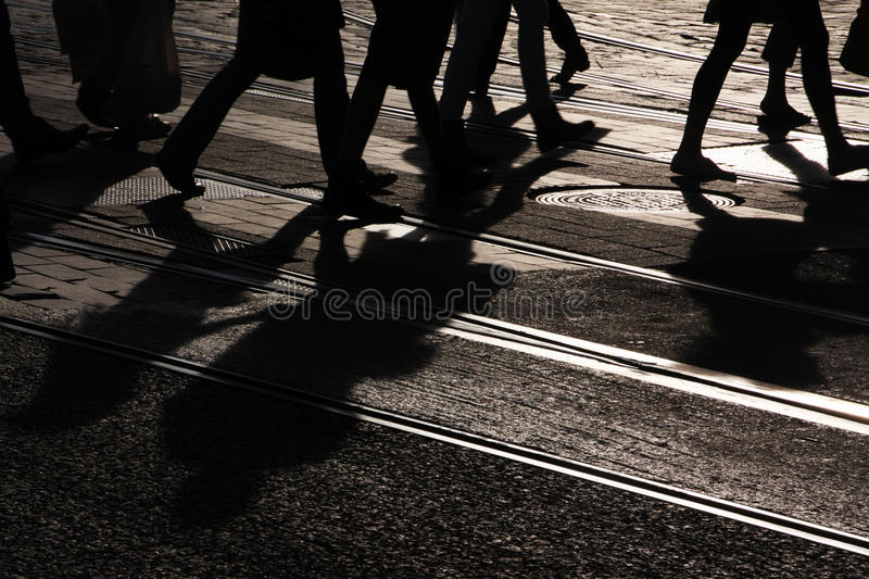 Pedestrians crossing. Silhouettes of pedestrians crossing the street stock photo