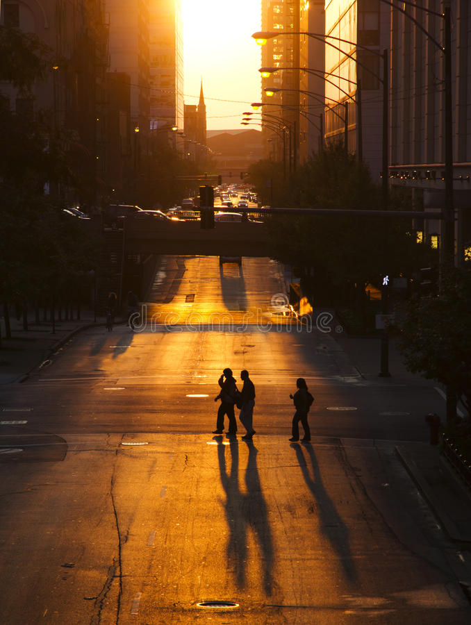 Pedestrians crossing street at sunset. Pedestrians in city crossing empty street at sunset royalty free stock image