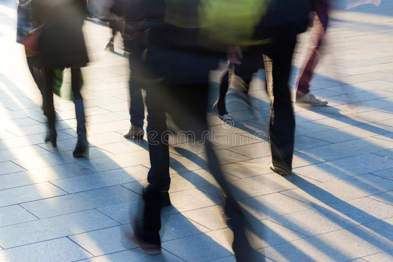 Crowd on the sidewalk at sunset with long shadows royalty free stock images