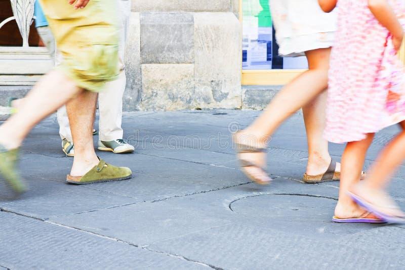 Pedestrians in a Italian city walking in a stone street.  stock photo