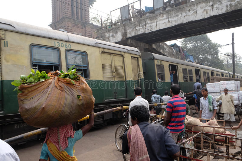 Pedestrians, rickshaws, cyclists waiting on railroad crossing in Kolkata stock photos