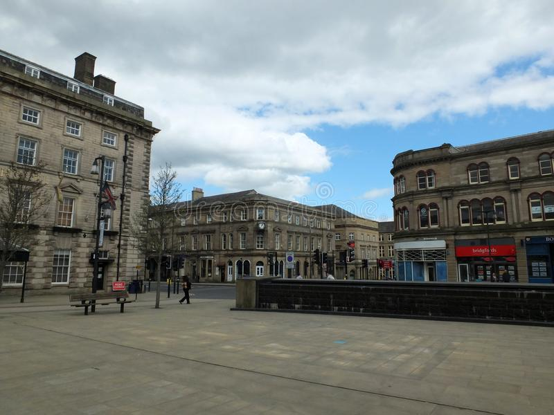 Pedestrians in St Georges Square walk past the historic old stone buildings around the pedestrian area. Huddersfield, West Yorkshire, England - April 26, 2018 stock photos