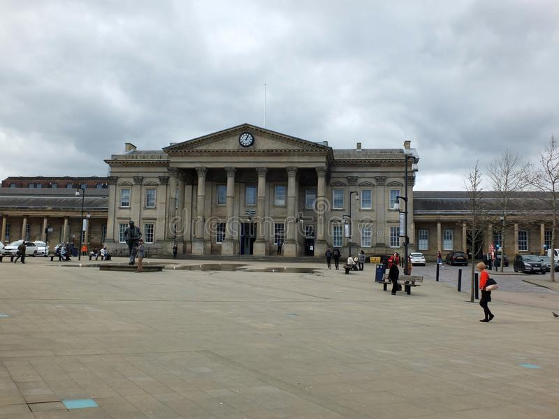 Pedestrians in St Georges Square walk past the historic railway station building. Huddersfield, West Yorkshire, England - April 26, 2018: Pedestrians in St royalty free stock photography