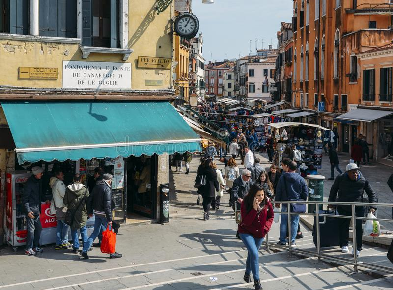 Pedestrians walk on busy street in the historic centre of Venice. Venice, Italy - March 28, 2018: Pedestrians walk on busy street in the historic centre of royalty free stock photo