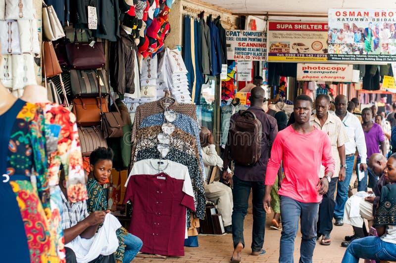 Pedestrians on Williams Street, Kampala. Pedestrians walking past shop exterior displays in William Street, downtown Kampala, Uganda stock photography