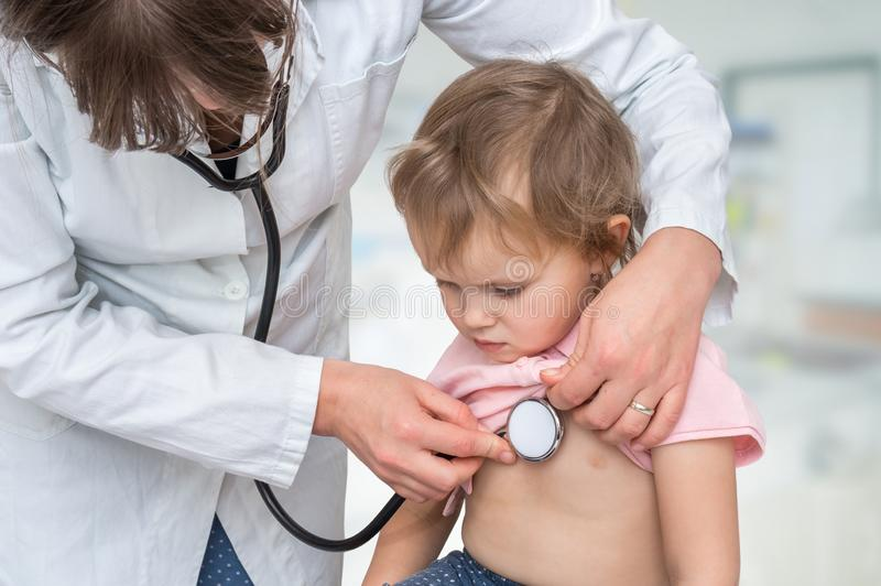 Pediater arts die een klein meisje onderzoeken door stethoscoop stock foto's