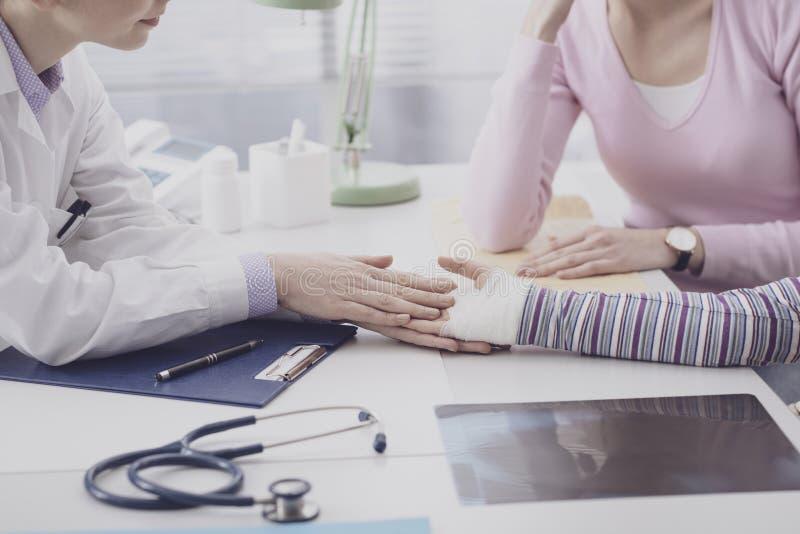 Pediater die een jong meisje met een verwonde pols onderzoeken stock afbeeldingen