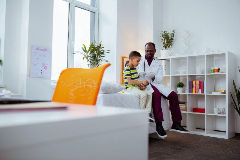 Pediater die glazen dragen die aan zijn kleine leuke patiënt spreken royalty-vrije stock afbeelding