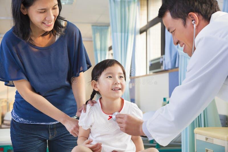 Pediater die meisje, haar moeder naast haar onderzoeken stock foto's