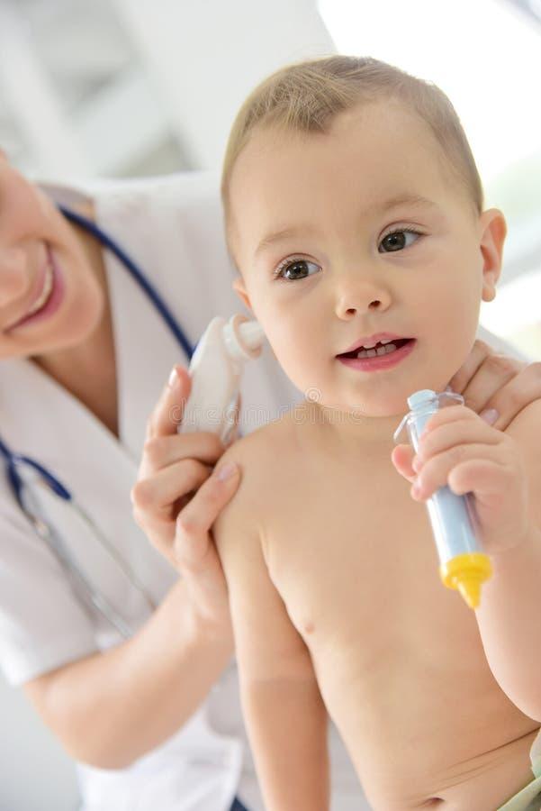 Pediater die temperatuur in het oor van de baby vergen royalty-vrije stock fotografie