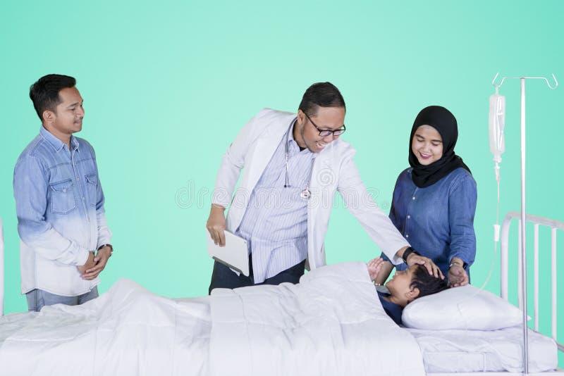 Pediatra amichevole che controlla il suo paziente sullo studio immagine stock libera da diritti