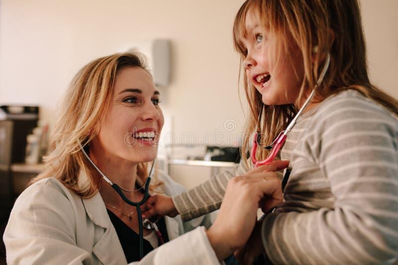 Pediatra amistoso que juega con su paciente de la muchacha en la clínica foto de archivo