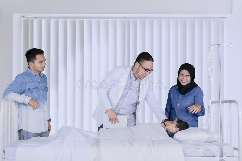 Pediatra asiatico che controlla il suo paziente immagini stock