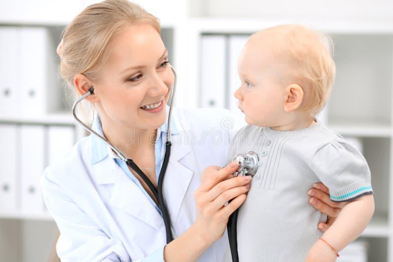 Pediatra bierze opiekę dziecko w szpitalu Mała dziewczynka jest egzamininuje lekarką z stetoskopem fotografia royalty free