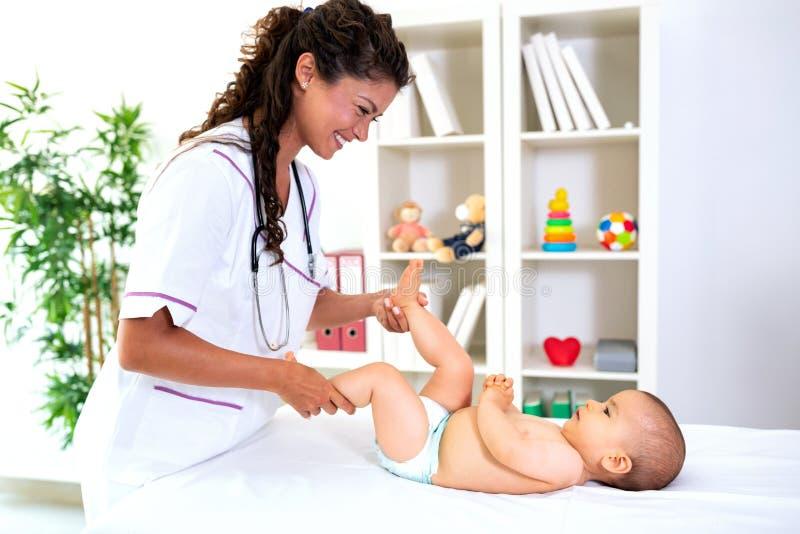 Pediatra bueno y que cuida que juega con su paciente foto de archivo