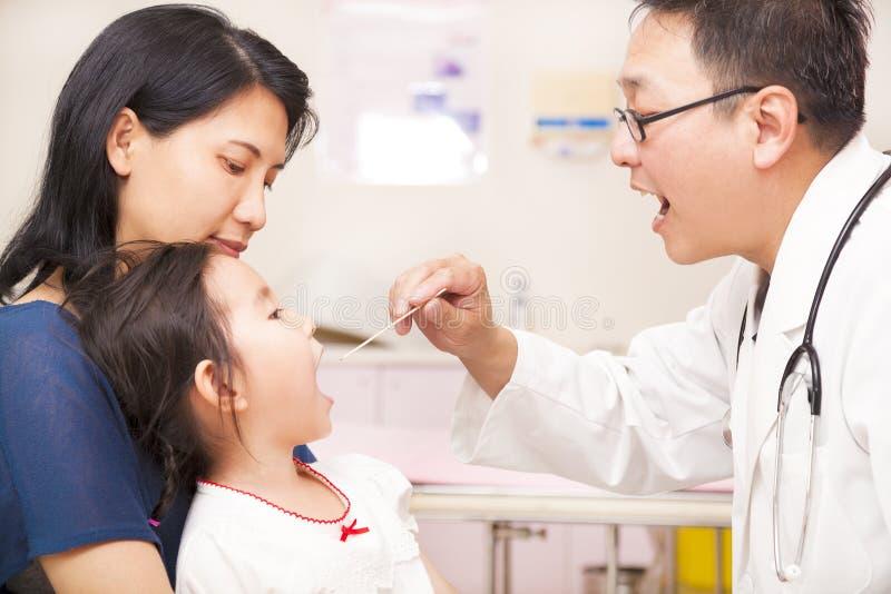 Pediatra che controlla la gola della bambina fotografia stock libera da diritti