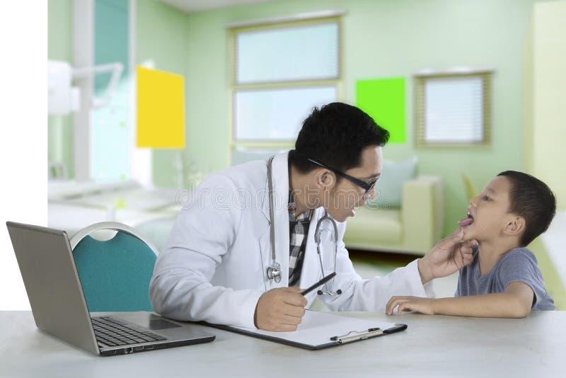 Pediatra che controlla lingua di un paziente in clinica fotografia stock libera da diritti