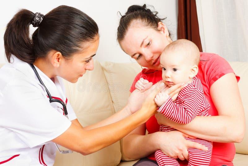 Pediatra che controlla un bambino immagini stock