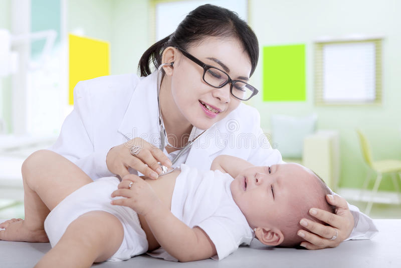 Pediatra che esamina un piccolo bambino immagine stock libera da diritti