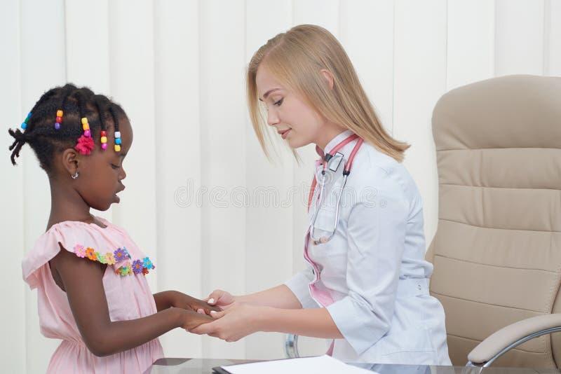 Pediatra da mulher, inspecionando pouca menina afro no armário imagens de stock royalty free