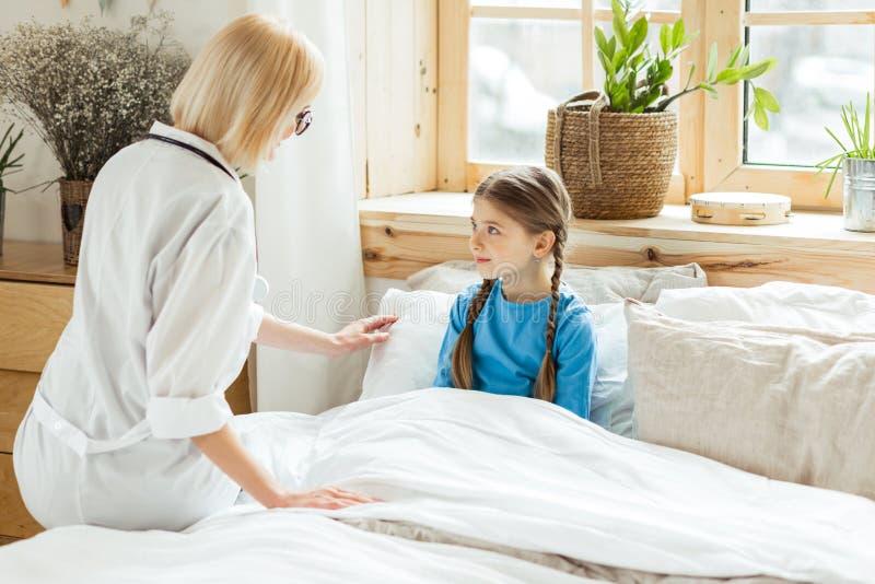 Pediatra de encantamento que põe a menina doente pequena a uma cama imagens de stock