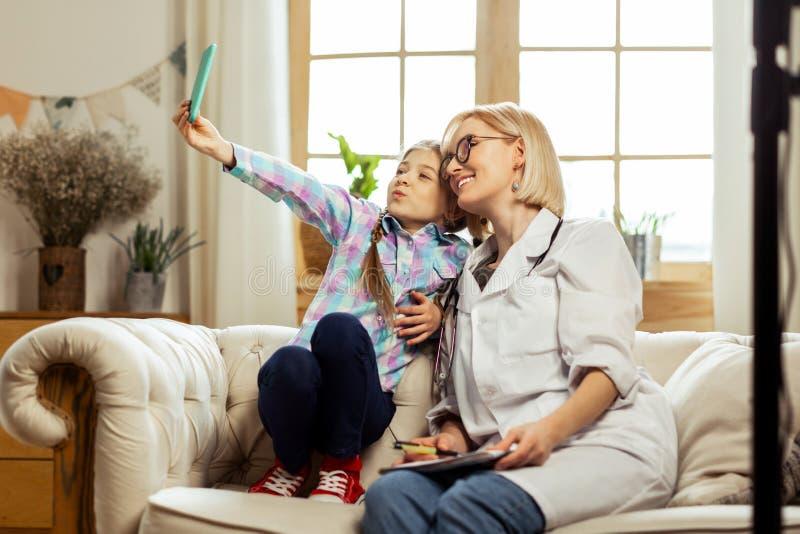 Pediatra de fascínio que faz selfies com uma menina de recuperação foto de stock