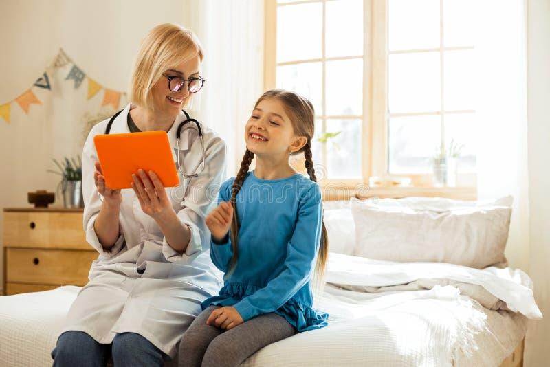 Pediatra de irradiação que ri e que tem o divertimento com uma menina pequena fotos de stock