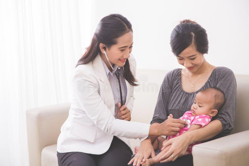 Pediatra de sexo femenino asiático que examina a un bebé en el la de la madre imagen de archivo