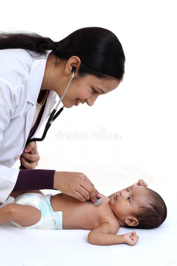 Pediatra de sexo femenino examinar al bebé recién nacido fotografía de archivo