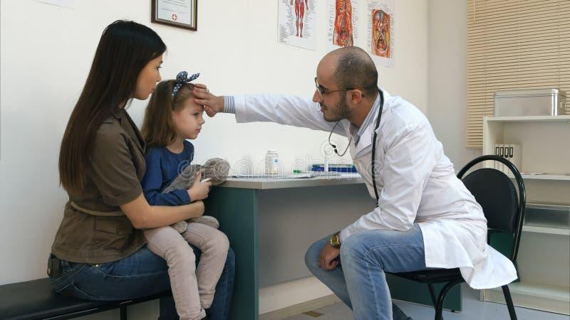 Pediatra de sexo masculino que comprueba la temperatura principal de la niña con su mano y que da su termómetro imagen de archivo libre de regalías