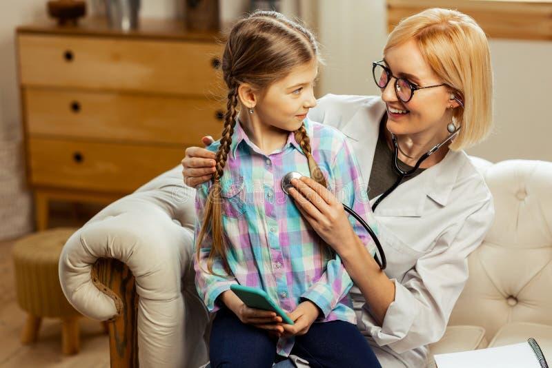 pediatra do Meados de-adulto que examina uma menina moreno doente que usa um estetoscópio fotos de stock