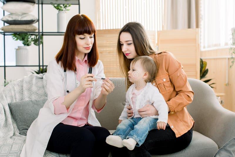 Pediatra doktorska egzamininuje temperatura mała dziewczynka w rękach matka Dziecka doktorski sprawdza dziecko zdjęcia royalty free