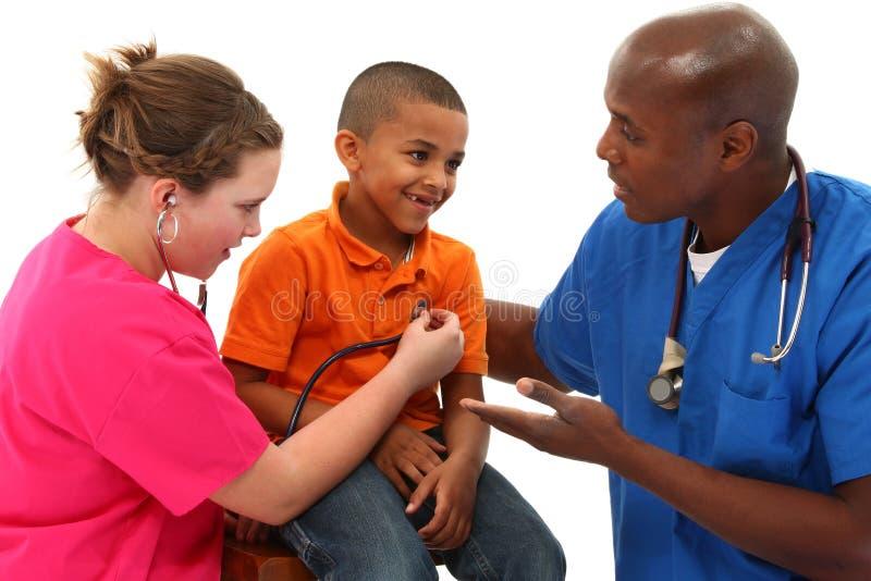 Pediatra ed infermiera con il giovane bambino nero immagini stock
