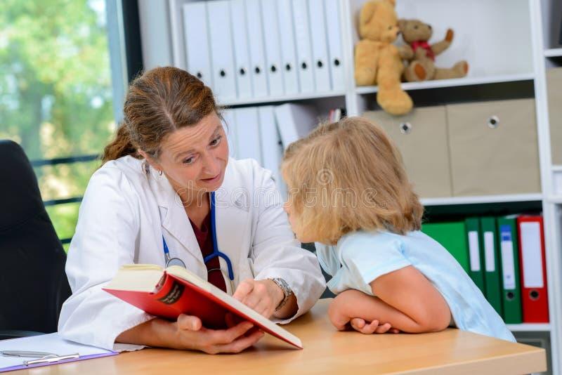 Pediatra en la capa blanca del laboratorio y el pequeño paciente imágenes de archivo libres de regalías