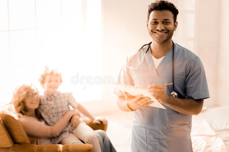 Pediatra encantado positivo que presenta en cámara foto de archivo