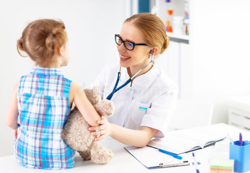 Pediatra feliz amistoso del doctor con la muchacha paciente del niño foto de archivo
