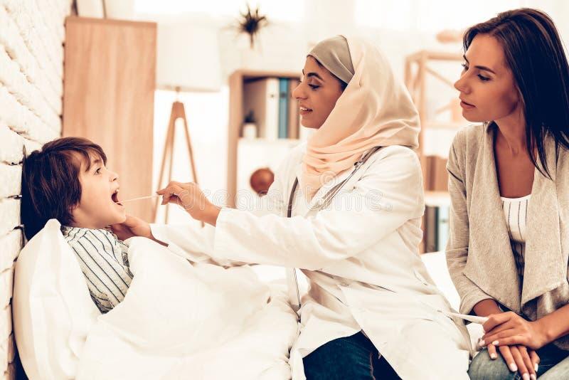 Pediatra muçulmano Examining Boy, doente da garganta foto de stock royalty free