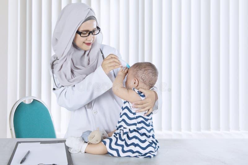 Pediatra musulmano che controlla il suo paziente nella clinica fotografia stock