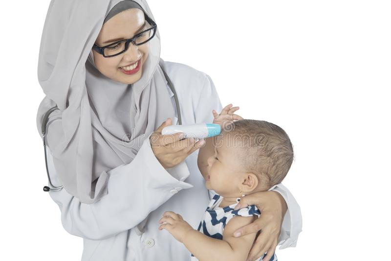 Pediatra musulmano che controlla il suo paziente sullo studio immagini stock