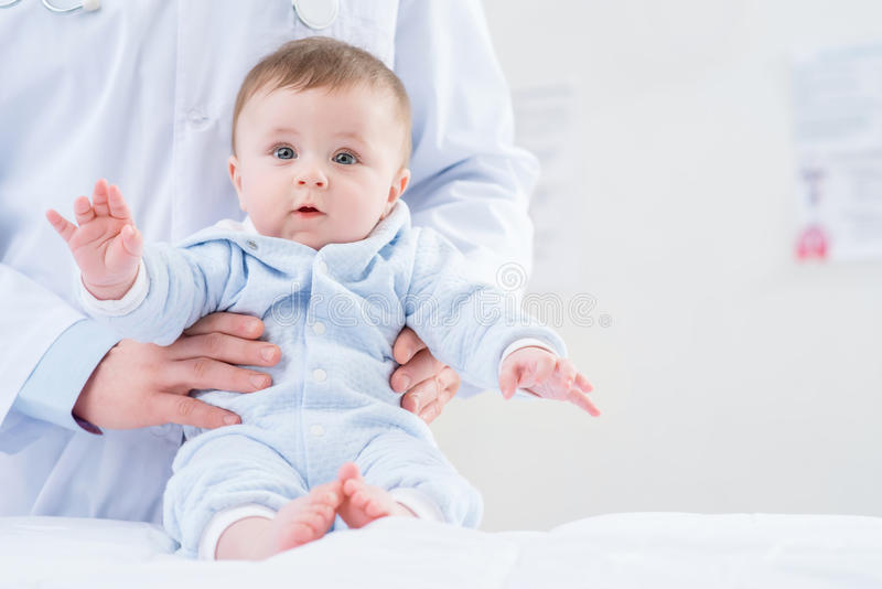 Pediatra profissional que guarda o infante foto de stock