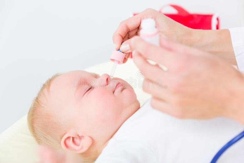 Pediatra que cancela o nariz de um bebê aplicando a solução salina imagens de stock royalty free