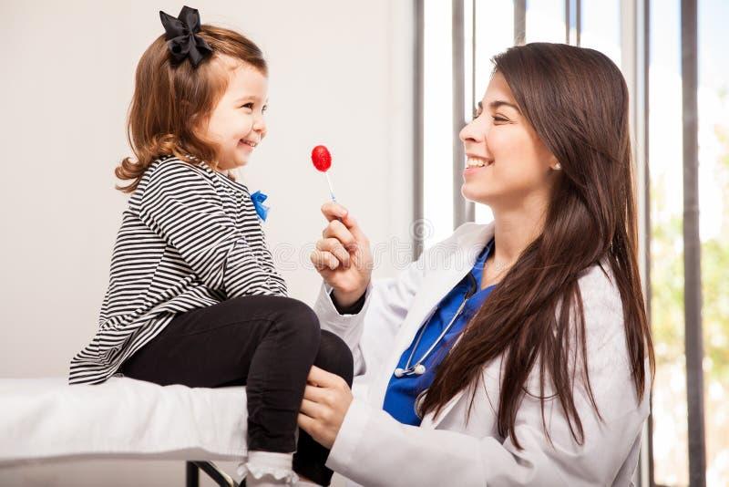 Pediatra que da una piruleta imágenes de archivo libres de regalías