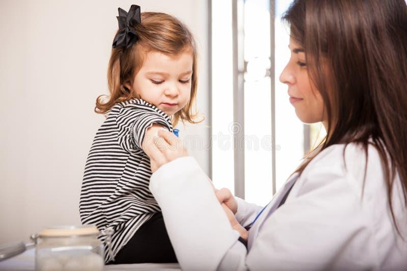 Pediatra que frota un poco de alcohol foto de archivo libre de regalías