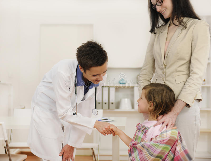 Pediatra que sacude la mano con el paciente del niño de la muchacha fotos de archivo libres de regalías