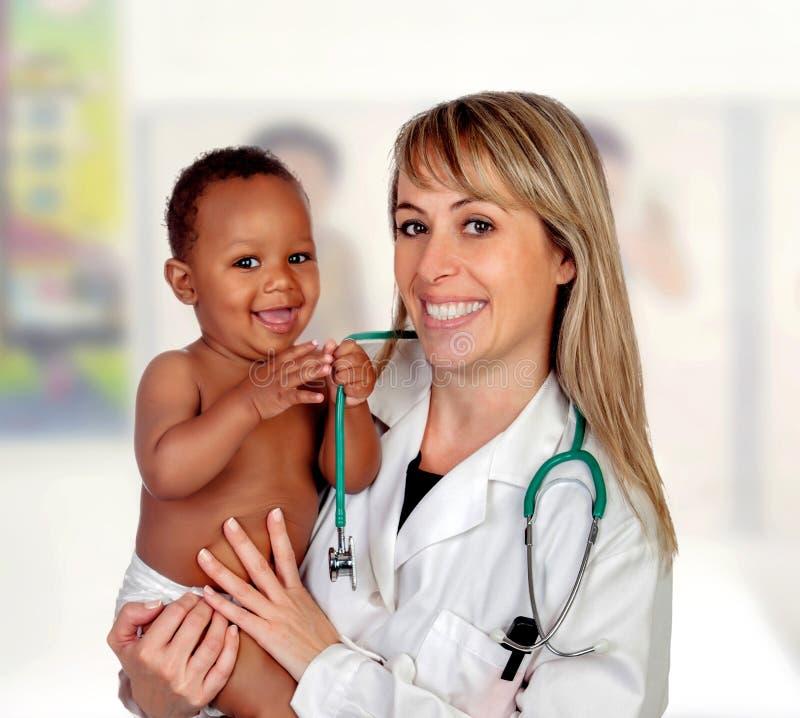 Pediatra rubio bonito con un bebé afroamericano hermoso en brazos imagenes de archivo
