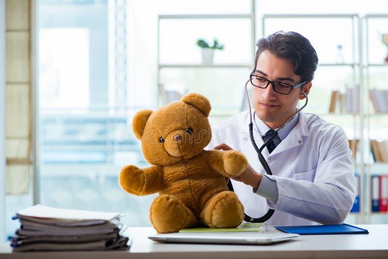 Pediatra z zabawkarskim obsiadaniem w biurze fotografia stock